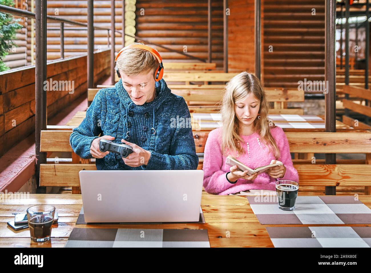Chico juega los juegos en un ordenador portátil en un café cercano a la chica está leyendo un libro concepto de desgaste. Foto de stock