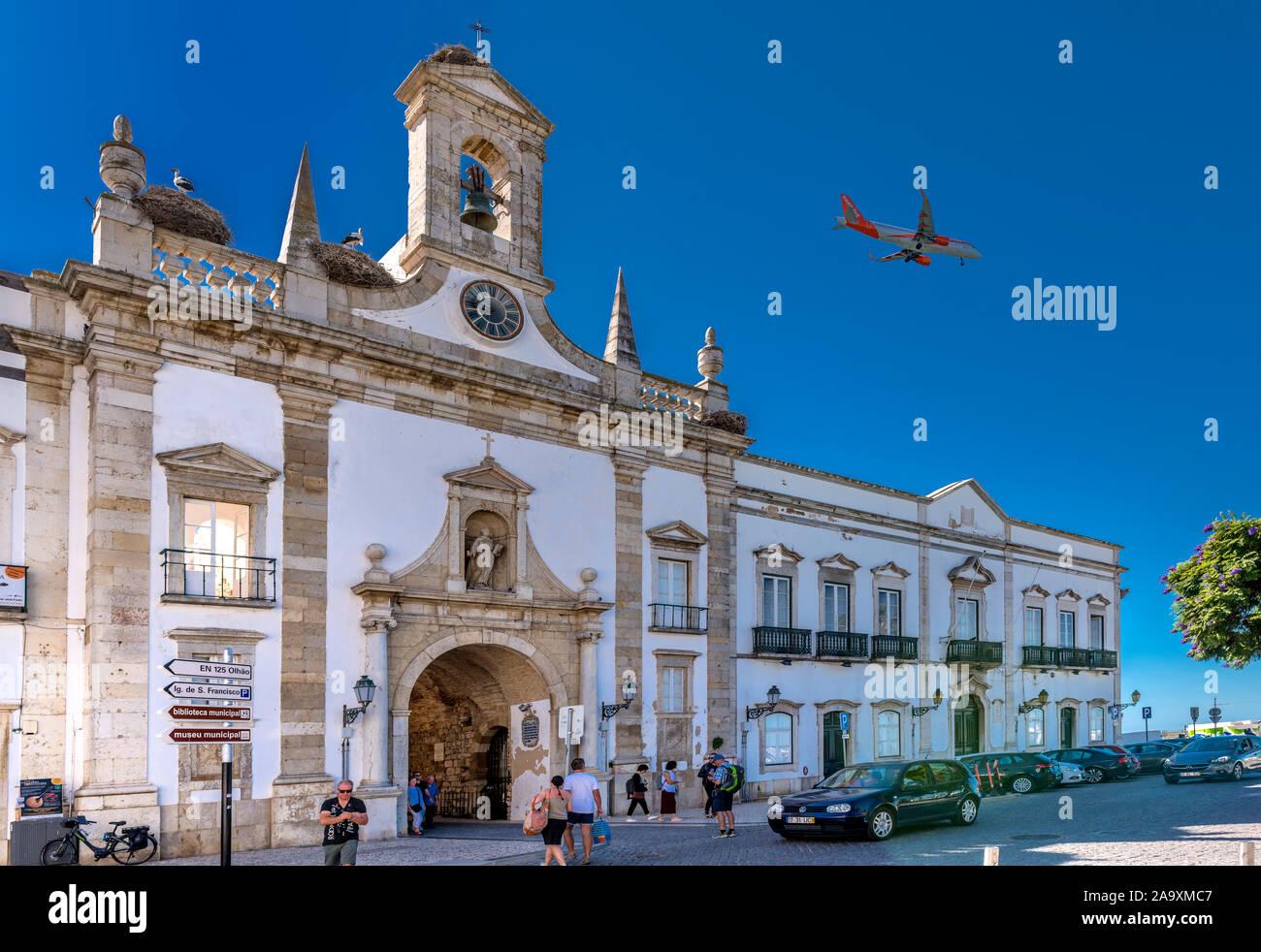 Avión de pasajeros volando sobre el punto de referencia de Faro, Arco da Vila entrando en tierra en el aeropuerto de Faro, Faro, Algarve, Portugal. Foto de stock