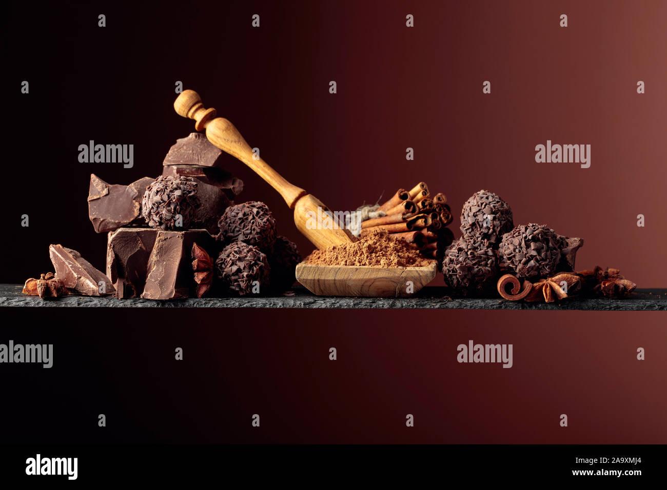 Trufas de chocolate con trozos de chocolate y especias. Chocolate, canela y anís sobre un fondo oscuro. Copie el espacio. Foto de stock