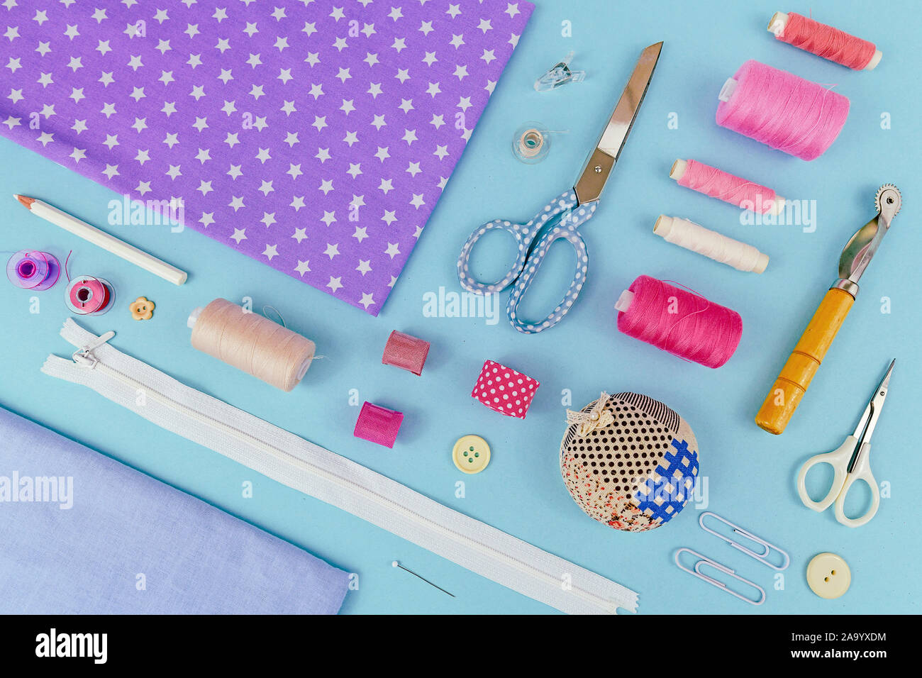 Planos generales sentar con diferentes herramientas como costura, tejido de hilo, zipper, tijeras, el carrete, hilo separador, almohadón o la segadora rotativa en b Foto de stock