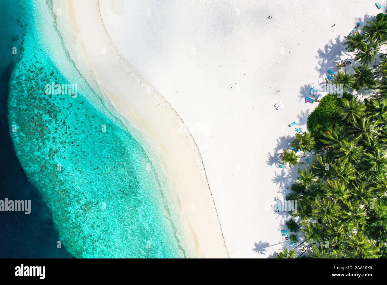 Vista superior de antena con zumbido de una exótica isla tropical paradisíaca con aguas cristalinas de color turquesa y playas de arena blanca pura Foto de stock