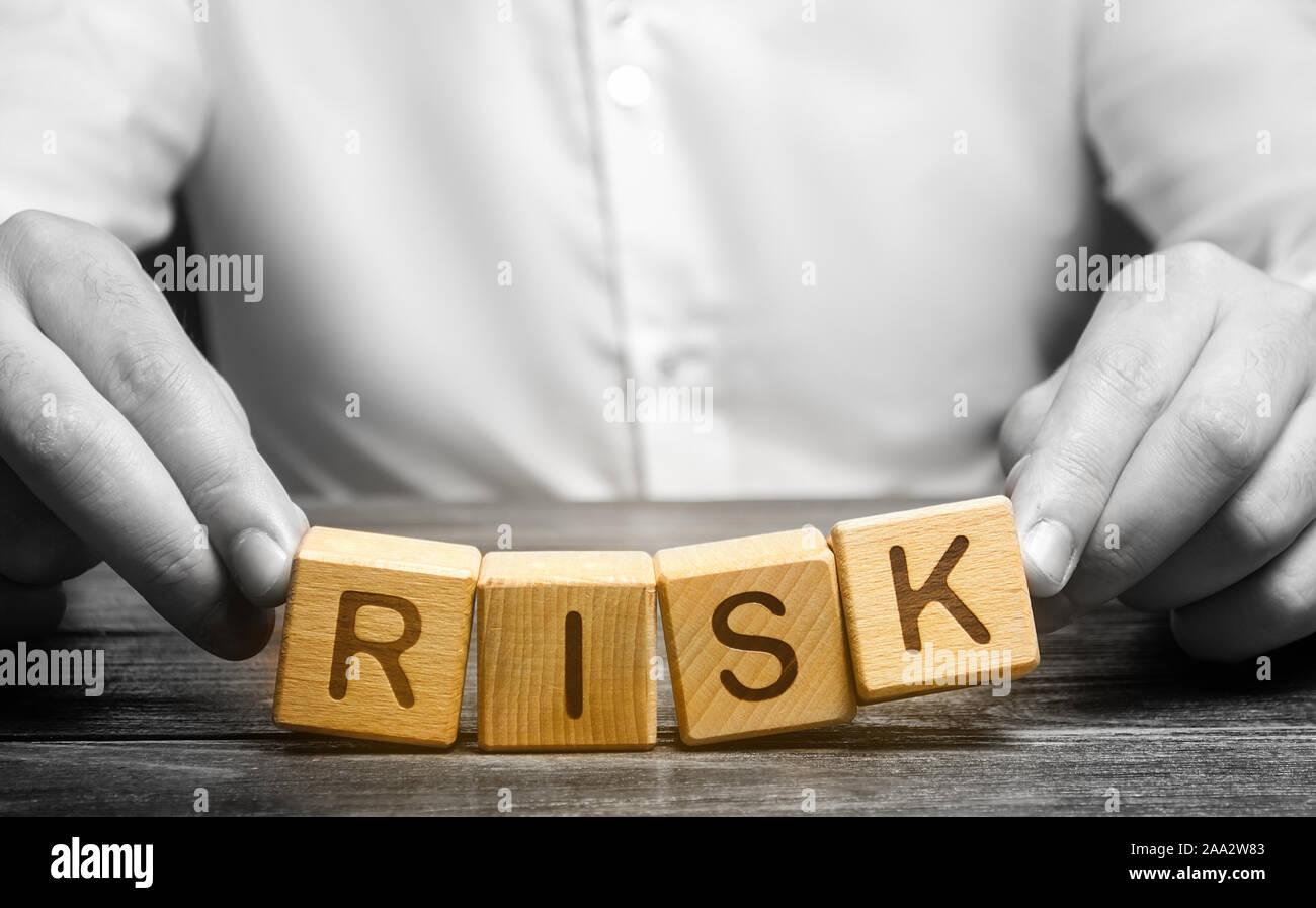 El hombre descuidadamente plantea la palabra riesgo. La prudencia y previsión de posibles problemas y perturbaciones. Planificación y estrategia de acción. Analytics. Alto riesgo Foto de stock