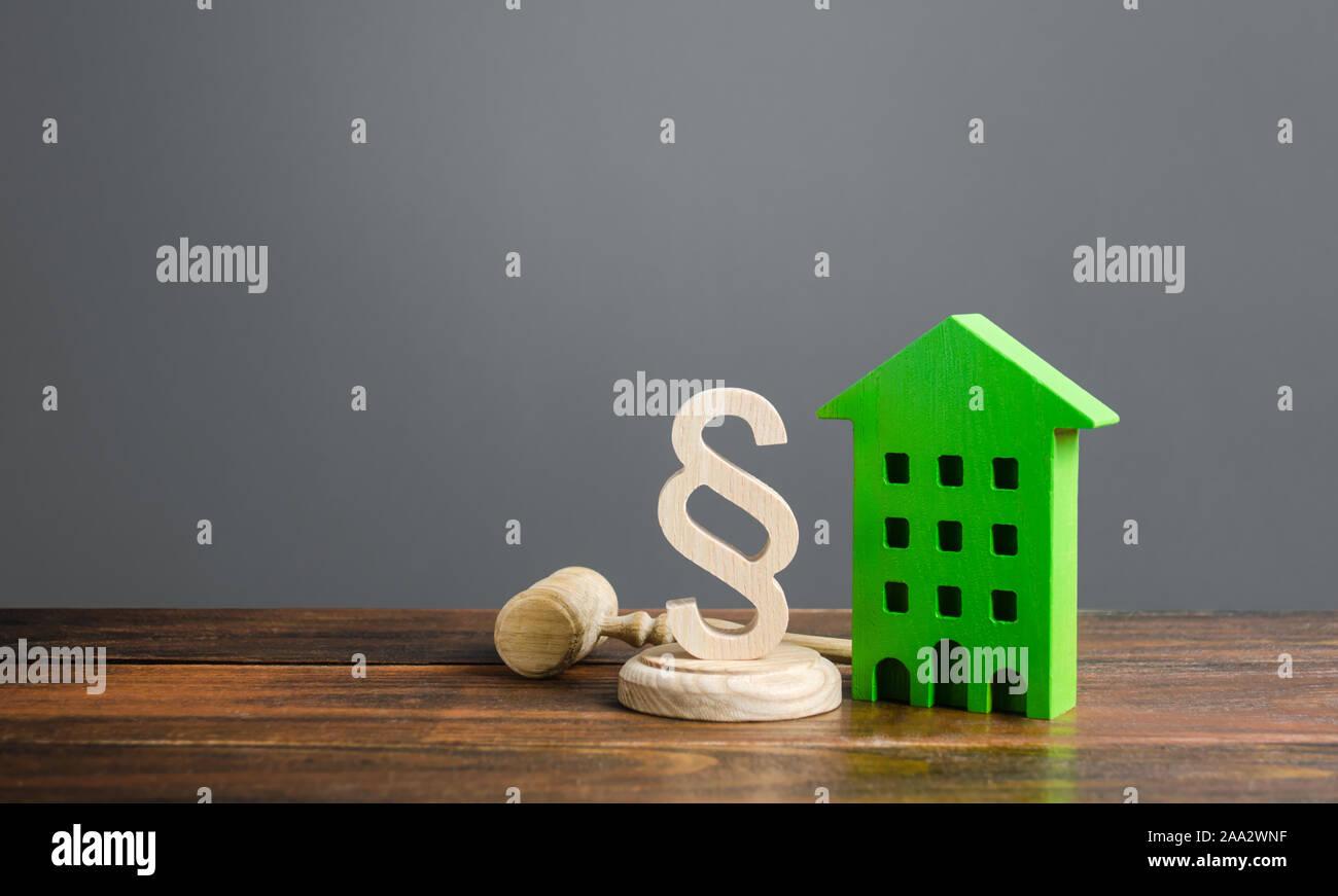 La casa verde y el párrafo figurine con un martillo de juez. Los litigios en disputas de bienes raíces y vivienda. Normas y reglas para la construcción y mantenimiento. Foto de stock