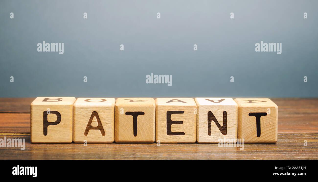 Bloques de madera con la palabra patente. Forma de propiedad intelectual. El documento que acredite el derecho de un inventor a su invención. Foto de stock