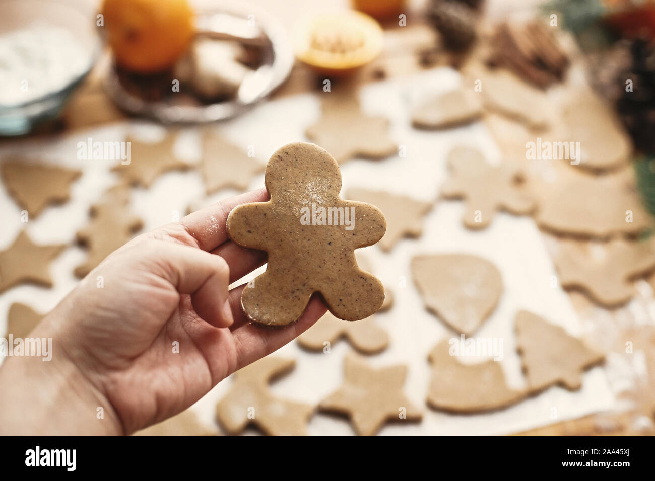 Mano sujetando las materias gingerbread man cookie en el fondo de la masa, cortadores de metal y anís, jengibre, canela, piñas, ramas de abeto sobre tabla rústica.Ma Foto de stock