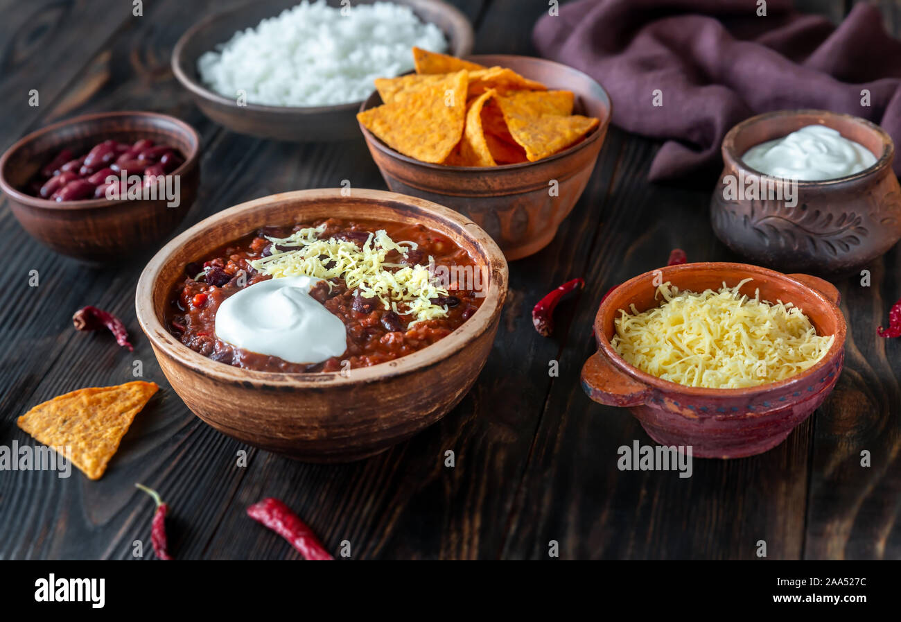 Tazón de Chili con carne con los ingredientes sobre una tabla de madera Foto de stock
