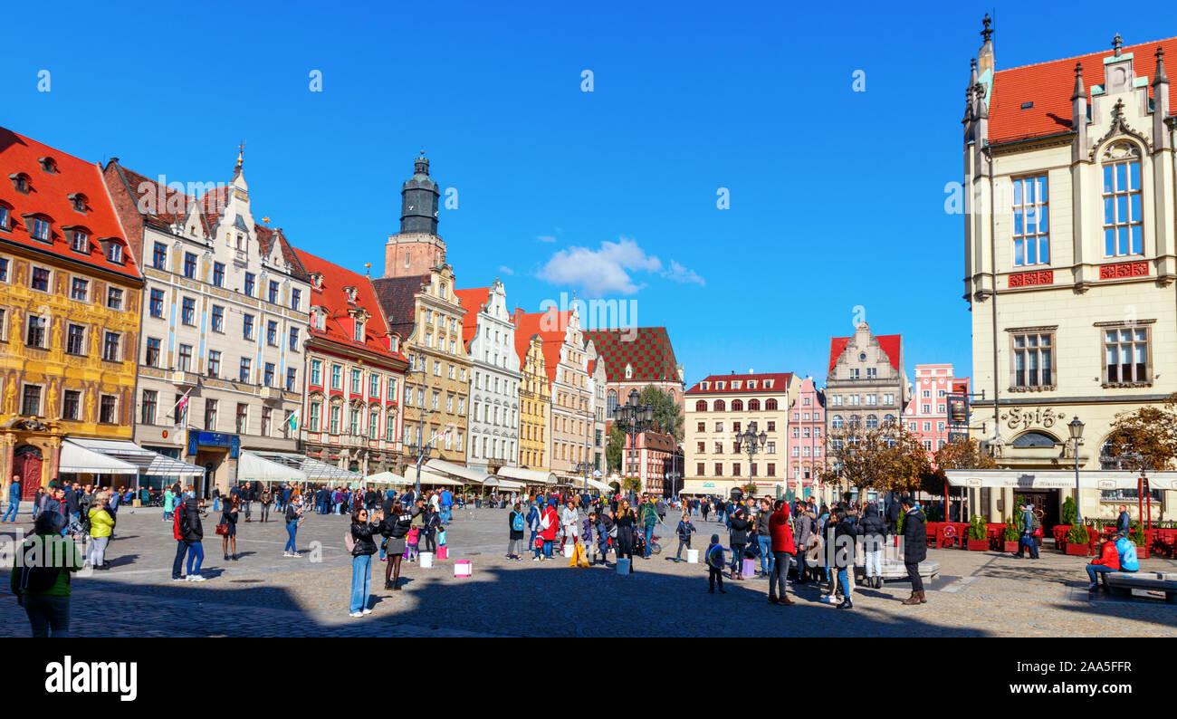 Turistas de paseo en la plaza del mercado de Wroclaw medieval, con sus coloridas casas y la iglesia de St Elizabeth campanario en el fondo. Polonia Foto de stock