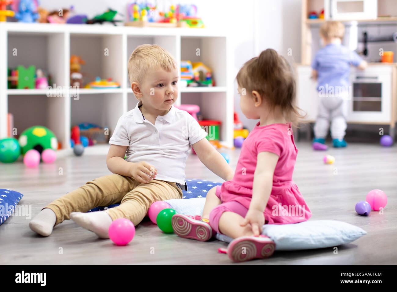 Los niños juegan con juguetes coloridos. Niño niña y niño pequeño niño en el kindergarten. Los niños juegan en la guardería o al preescolar. Foto de stock