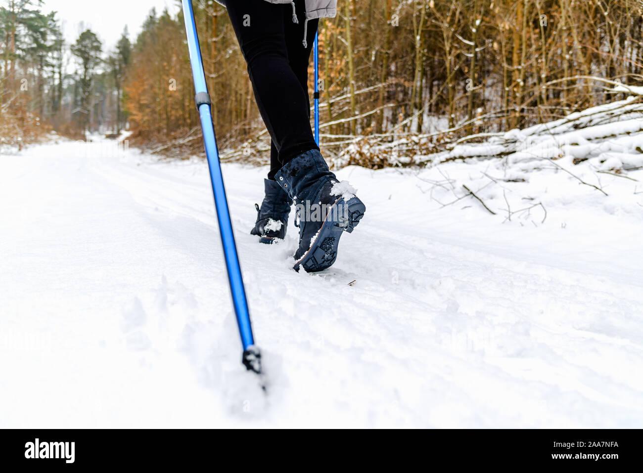 Mujer activa de caminar en la nieve. Botas y piernas detalle