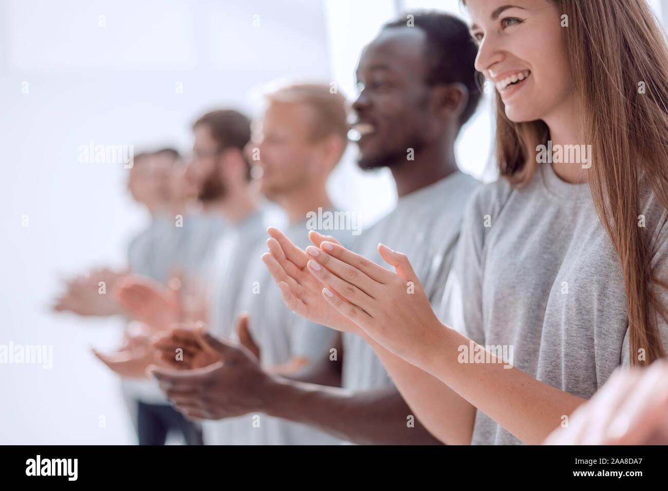 Imagen de un grupo de jóvenes de pie en una fila aplaudiendo. Foto de stock