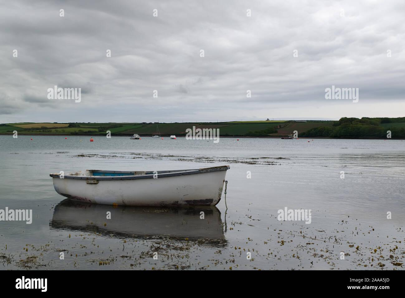 Bote de remos blancos amarrados con reflejos en el agua con los botes y tierras fuera de foco en el fondo. Concepto de pesca Foto de stock