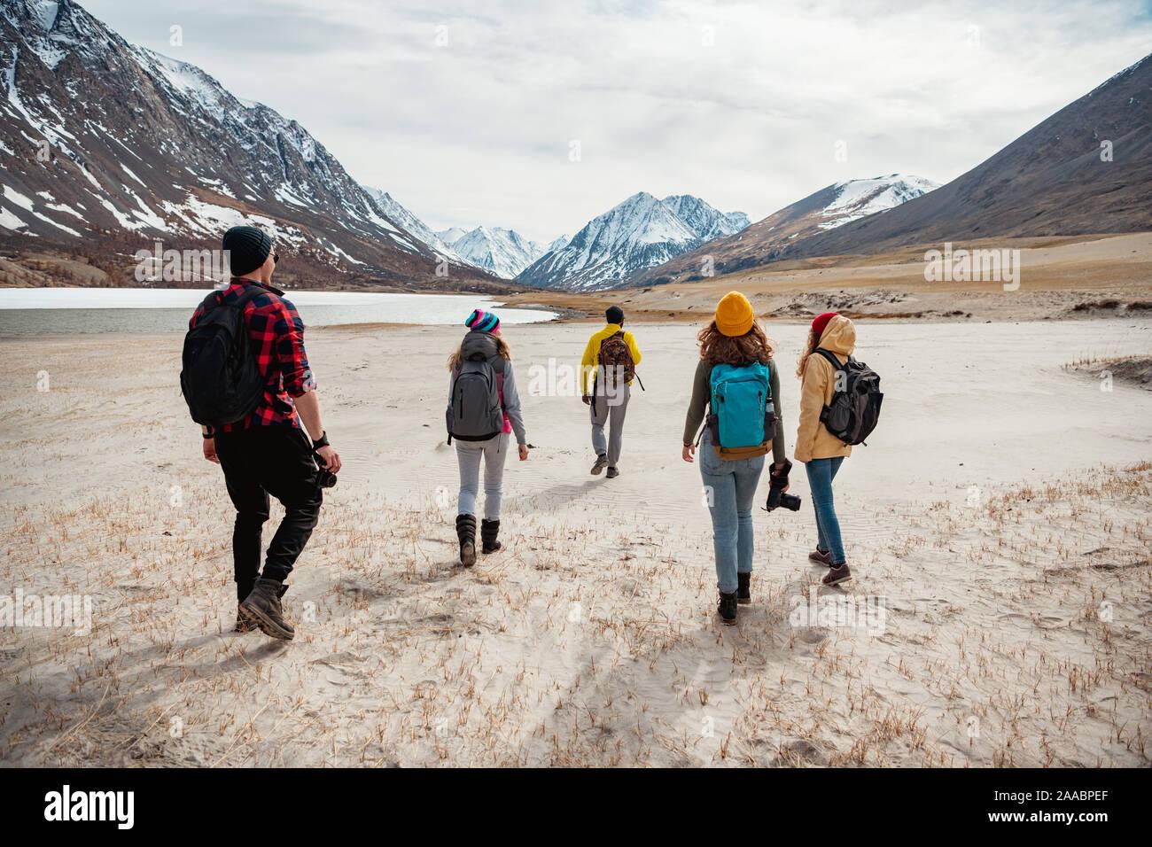 Grupo de jóvenes amigos excursionistas está caminando en las montañas valley Foto de stock