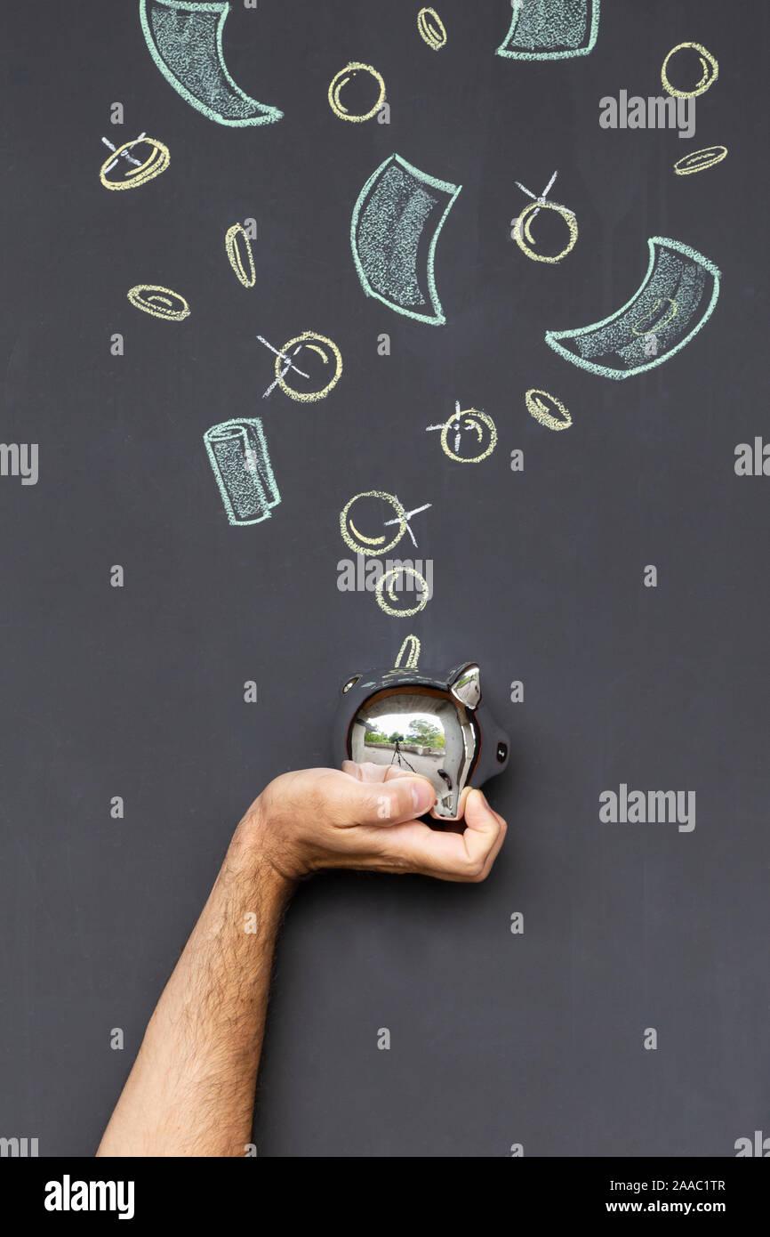 Concepto de ahorrar dinero con una hucha de plata celebrada en una mano delante de una pizarra con monedas y billetes dibujados a mano Foto de stock