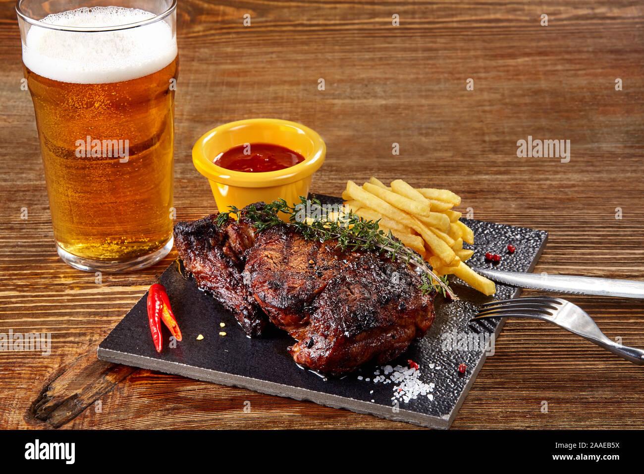 Vaso de cerveza con filete gourmet y patatas fritas en el fondo de madera. Foto de stock