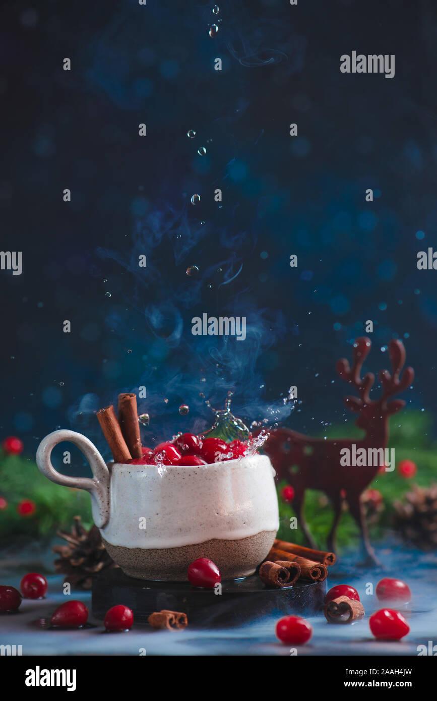 Bebida de invierno de arándano con gotas de agua, la canela, el vapor de agua, y un ciervo decorativos de madera. Foto de stock
