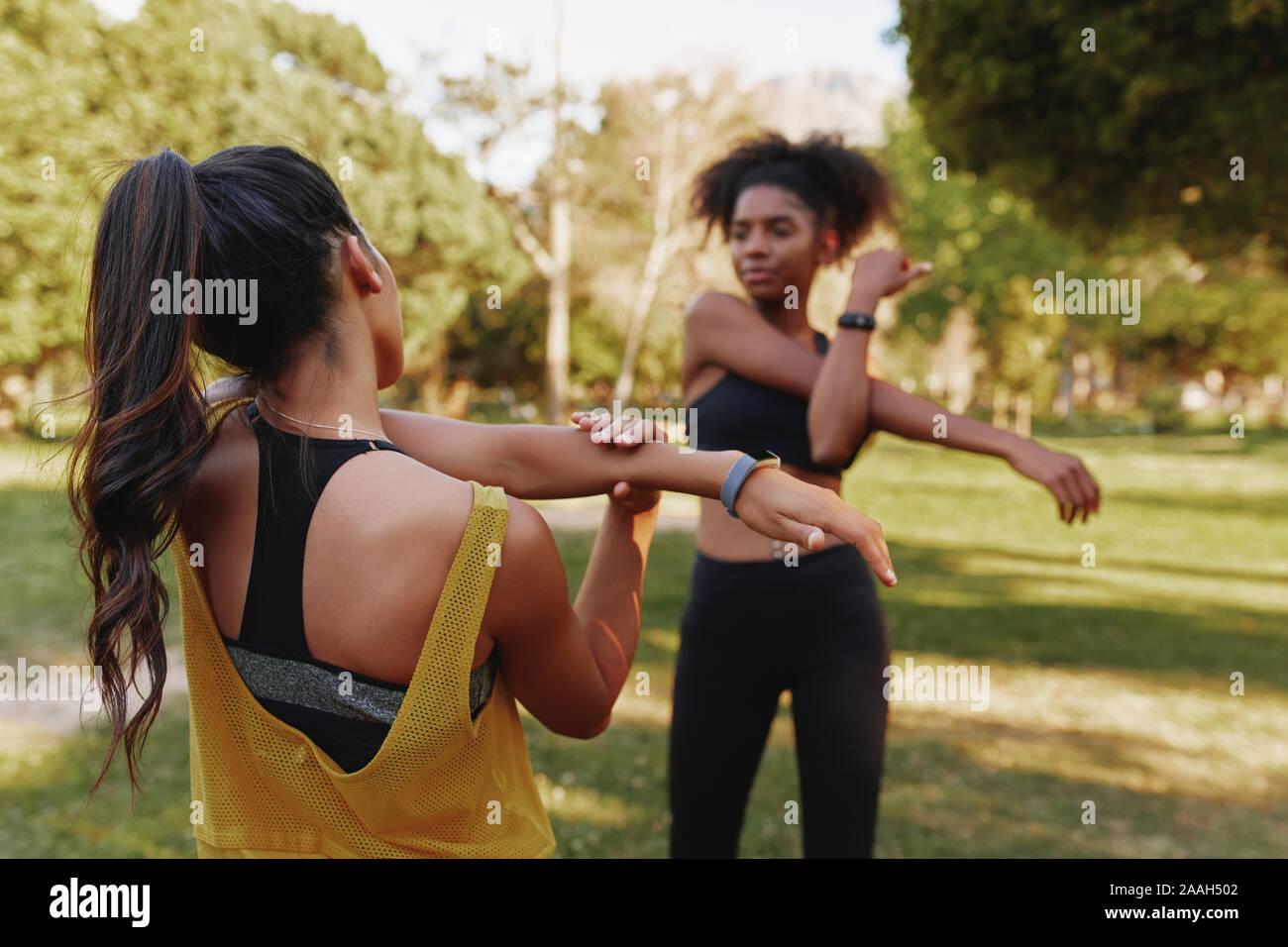 Dos jóvenes de gimnasia deportiva femenina diversos amigos de estirar sus músculos en el parque en un día de verano - dos amigos que trabajan juntos Foto de stock