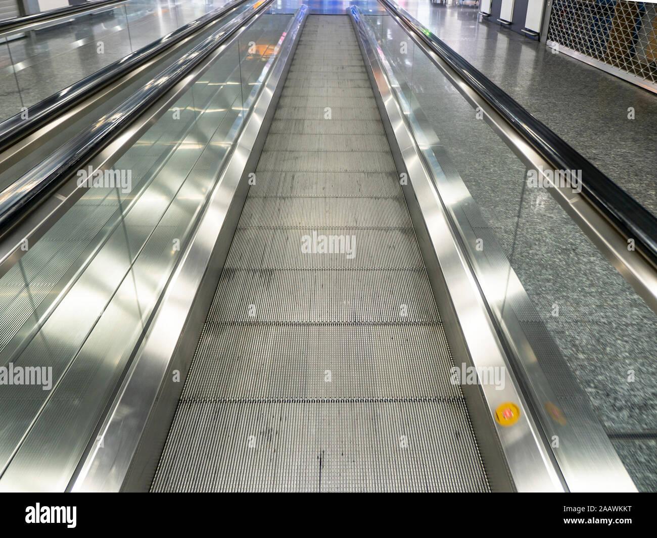 Perspectiva decreciente de andén móvil vacía en el aeropuerto Foto de stock