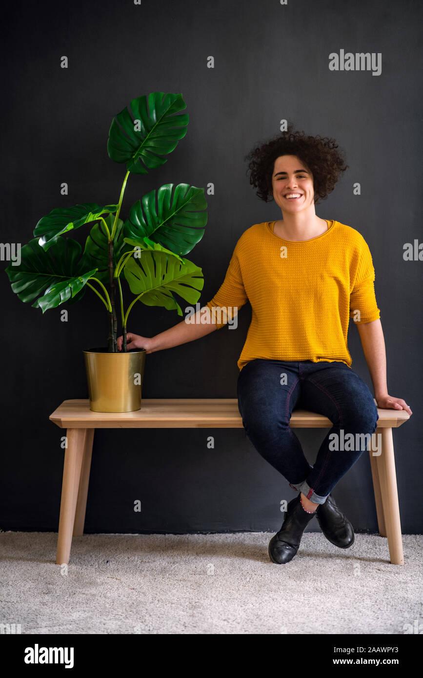 Retrato de mujer joven sosteniendo una planta de casa y mirando a la cámara Foto de stock