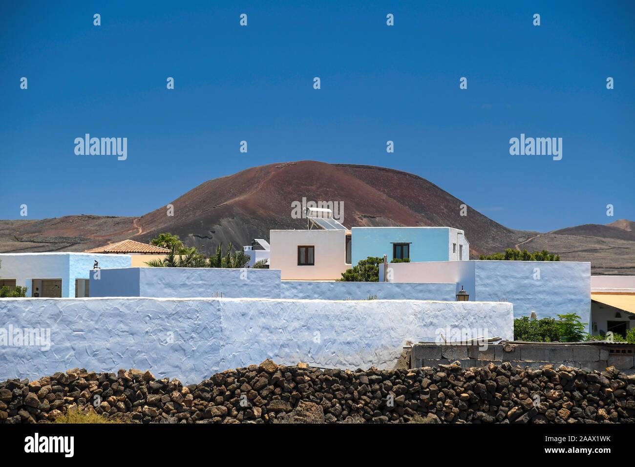 Vista de una típica aldea marina con cuadradas pequeñas casas blancas, cielo azul y marrón de colinas en el fondo, y el muro de piedra. Residencial complejo tropical Foto de stock
