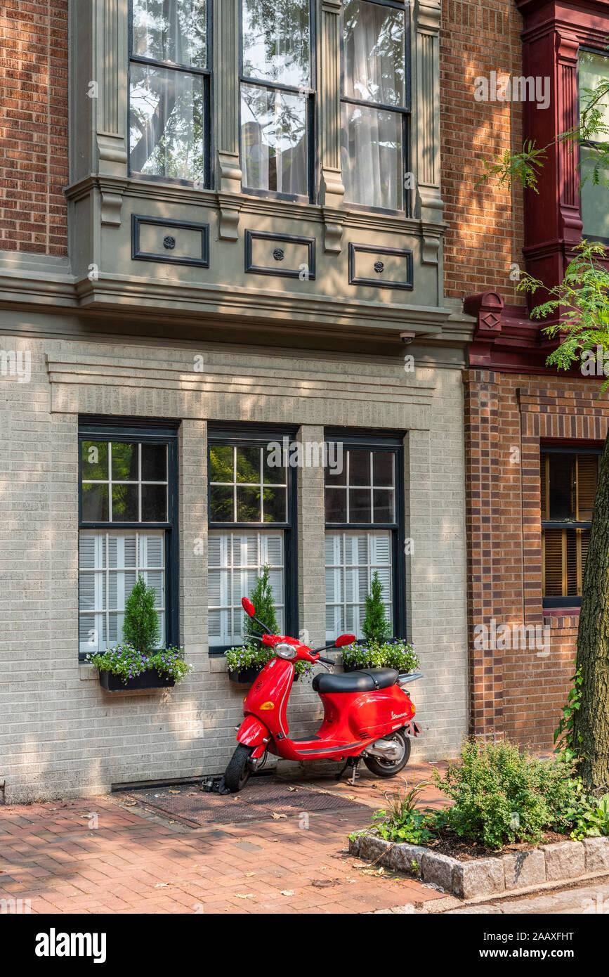 Un rojo vibrante Vespa scooter aparcado fuera una fila casa en South 4th Street, Society Hill. Foto de stock