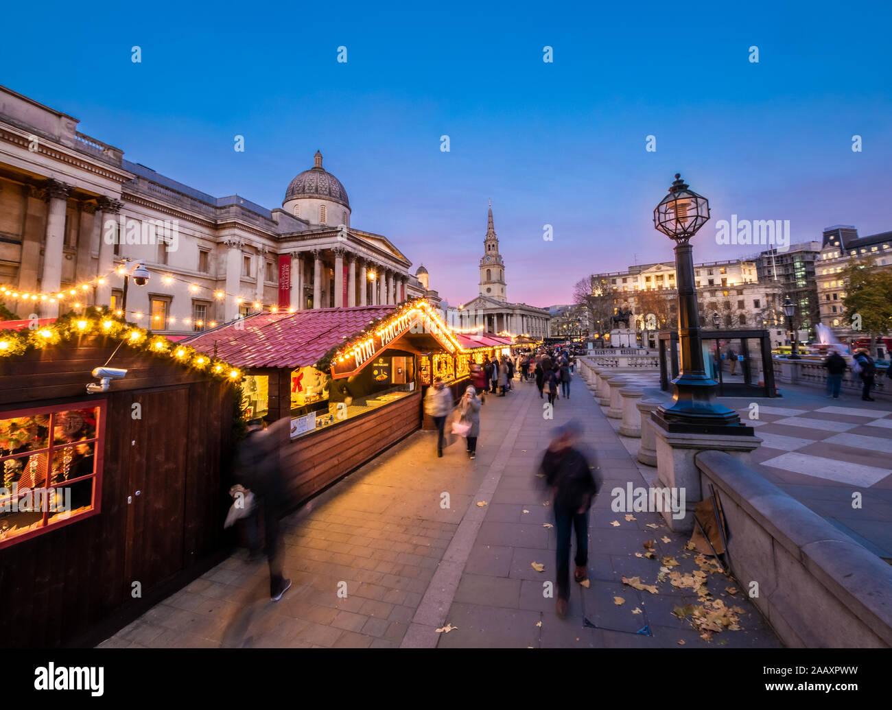 Londres, Inglaterra, Reino Unido - escena navideña al aire libre en Trafalgar Square Market a la hora azul en la temporada de invierno Foto de stock