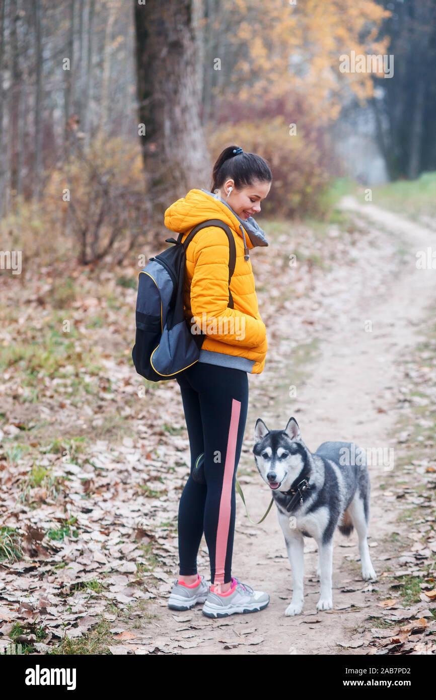 La mujer va con un perro a caminar en el parque en otoño Foto de stock