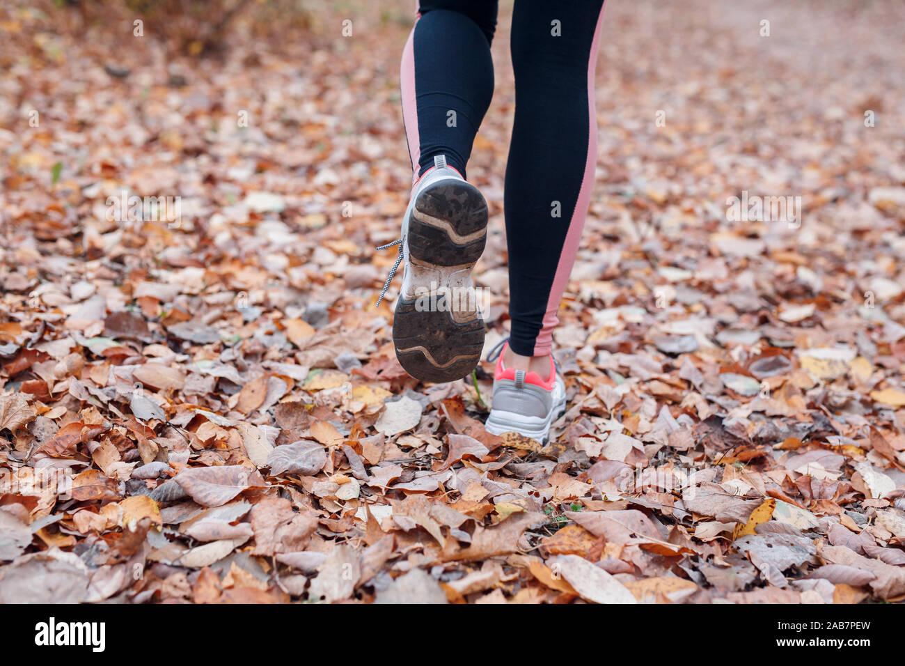 Cerca de los pies de un corredor corriendo en hojas de otoño en el parque Foto de stock
