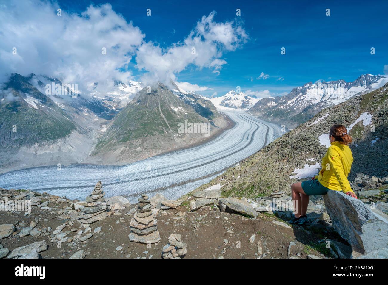 Vista lateral de la mujer sentada sobre las rocas, admirando el Glaciar Aletsch desde el punto de vista Eggishorn, Alpes Berneses, cantón de Valais, Suiza, Europa Foto de stock