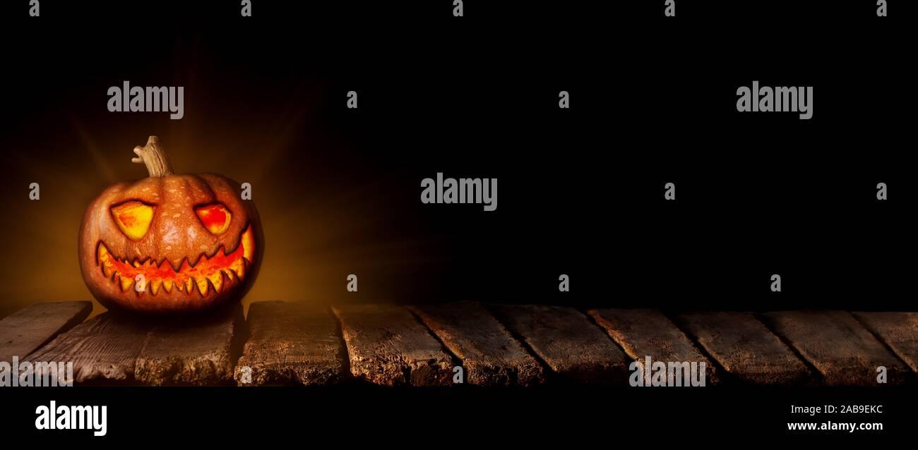 Calabaza de Halloween, Jack Oâ.Linterna brillando sobre la mesa de madera en un ambiente de miedo, embrujada. Foto de stock