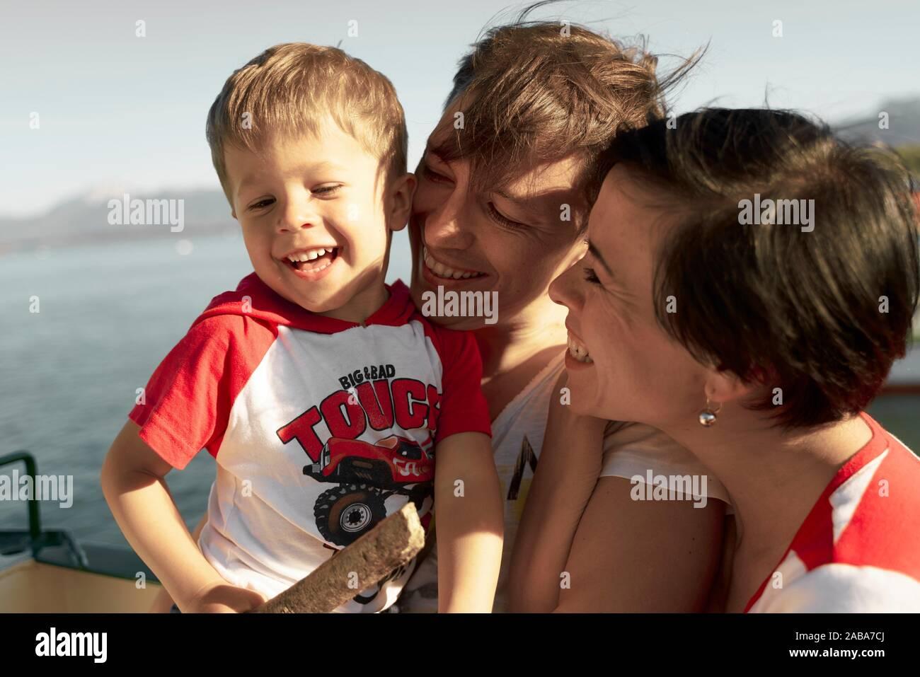 Felices padres con HIJO, NIÑO NIÑO, durante el día de viaje, una escapada familiar, en ferry en Chiemsee, Baviera, Alemania Foto de stock