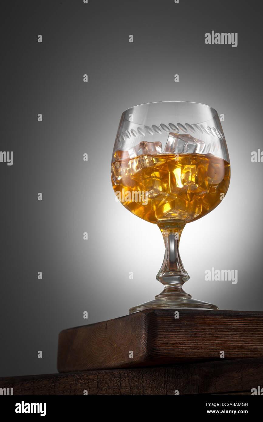 Bebida de naranja con hielo en winglass sobre la mesa de madera Foto de stock