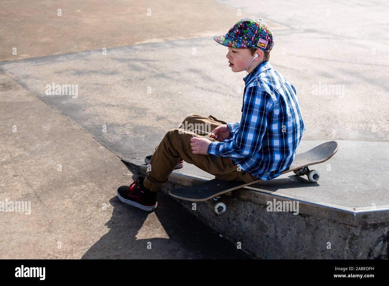 Un pequeño y lindo niño con síndrome de Asperger, autismo, ADHD caballo alrededor del skatepark escuchando música y practicar trucos, baje las escaleras, Ollie etc Foto de stock