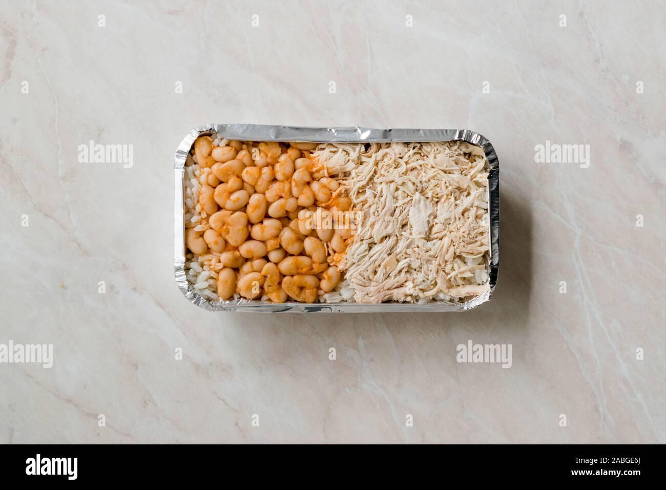 Llevar comida rápida turca de pollo, arroz y frijoles al horno / Tavuk Pilav Pilaf o en una caja de plástico / paquete contenedor. Plato tradicional. Foto de stock