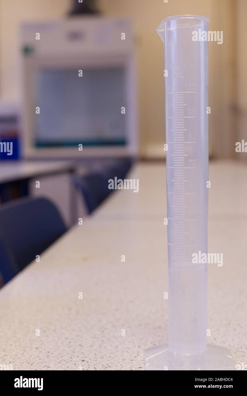 Medición del volumen de agua en una probeta de plástico en un laboratorio de ciencias de la escuela. Los mililitros de líquido. Una investigación práctica configurar Foto de stock