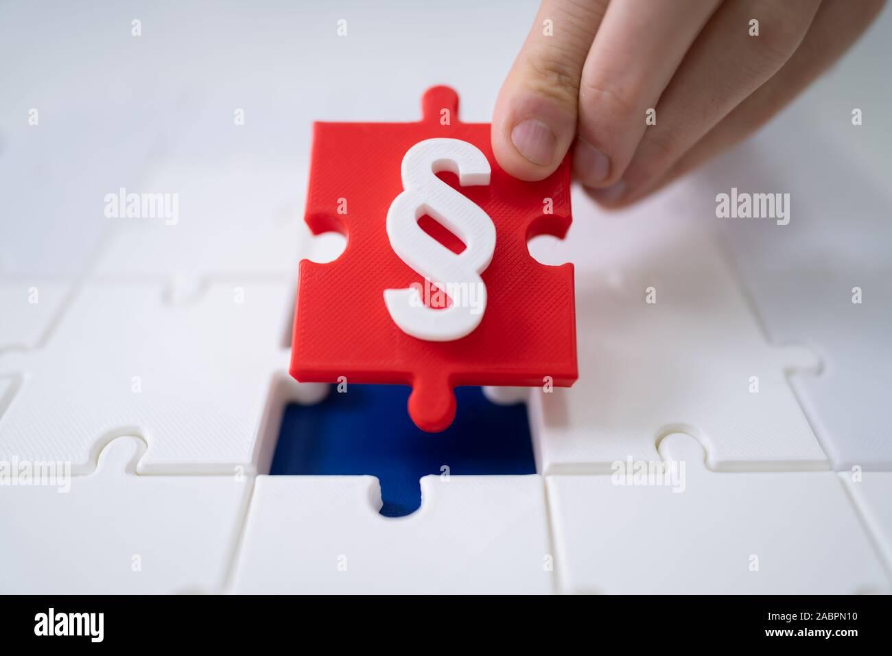 Una persona que conecte la última pieza roja con el símbolo de párrafo en los rompecabezas Foto de stock