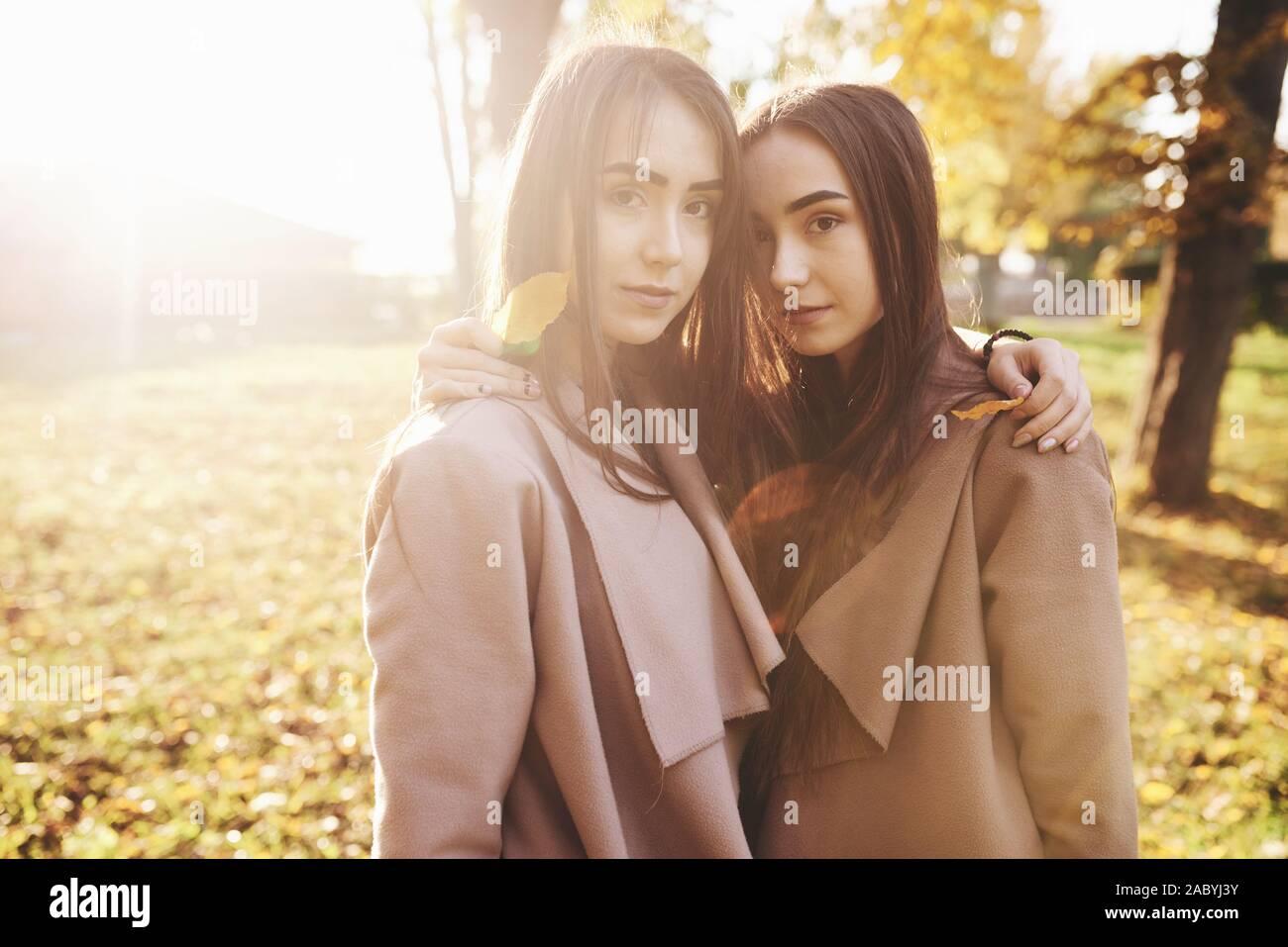 Dos niñas joven morenita muy cerca de pie se dirigió a cada uno de otros, tomados de la mano con las hojas sobre sus hombros, vistiendo chaqueta casual, tocando los jefes Foto de stock