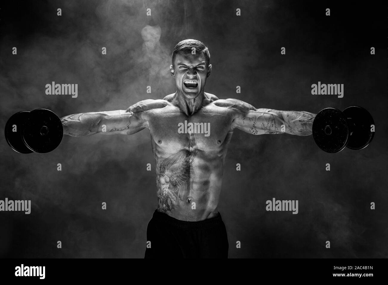 Muy musculoso guy culturista, ejecutar el ejercicio con pesas, el músculo deltoides del hombro. Sream para la motivación. Rodada en estudio de antecedentes de humo. Foto de stock