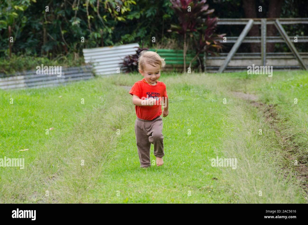 Un uno-año-viejo muchacho de la parte asiática jugando fuera discurre por un camino cubierto de hierba, Isla Grande. Foto de stock