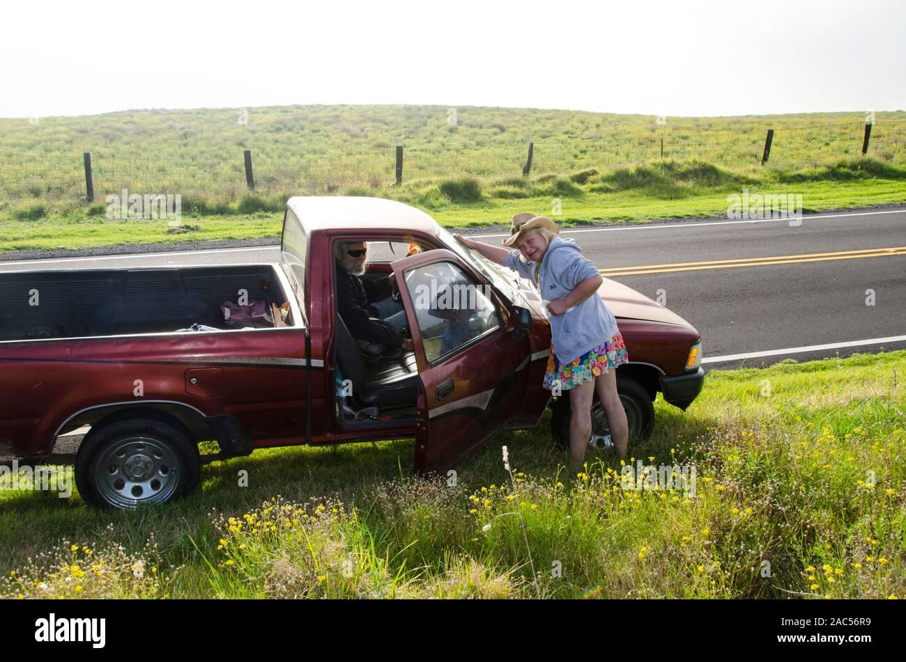 Una linda pareja de ancianos con un camión rojo a lo largo de pausa Saddle Road, Isla Grande. Foto de stock