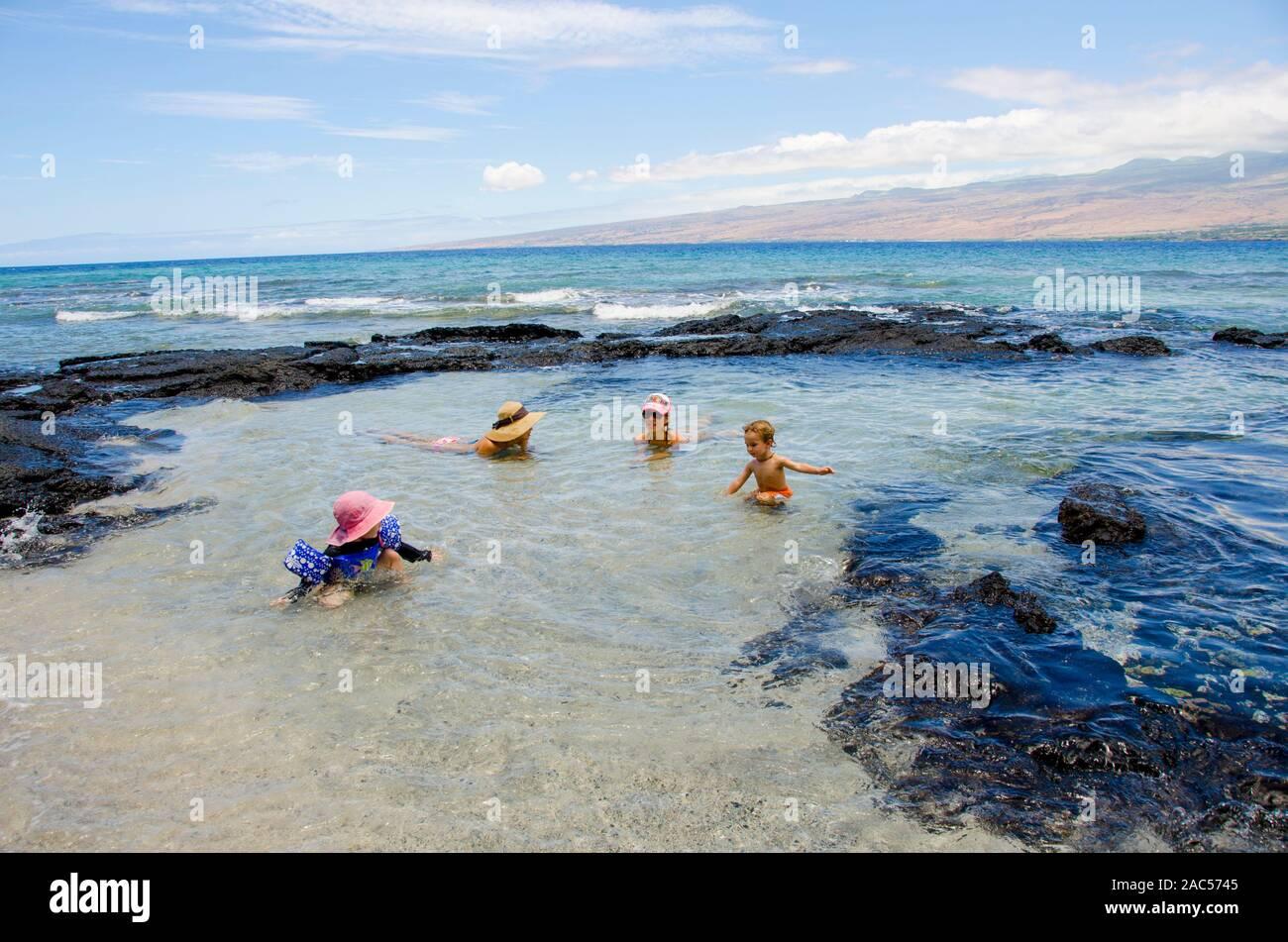 Una niña con el brazo floaties juega con un joven, mientras sus madres mirar en una piscina de marea en Puako, South Kohala, Isla Grande. Foto de stock