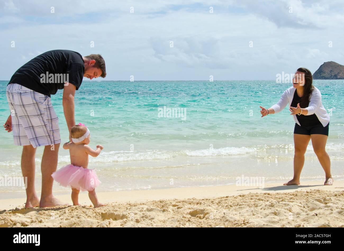 Una madre y un padre, alentando su joven hija a caminar a la orilla de la playa Lanikai, O'ahu. Foto de stock