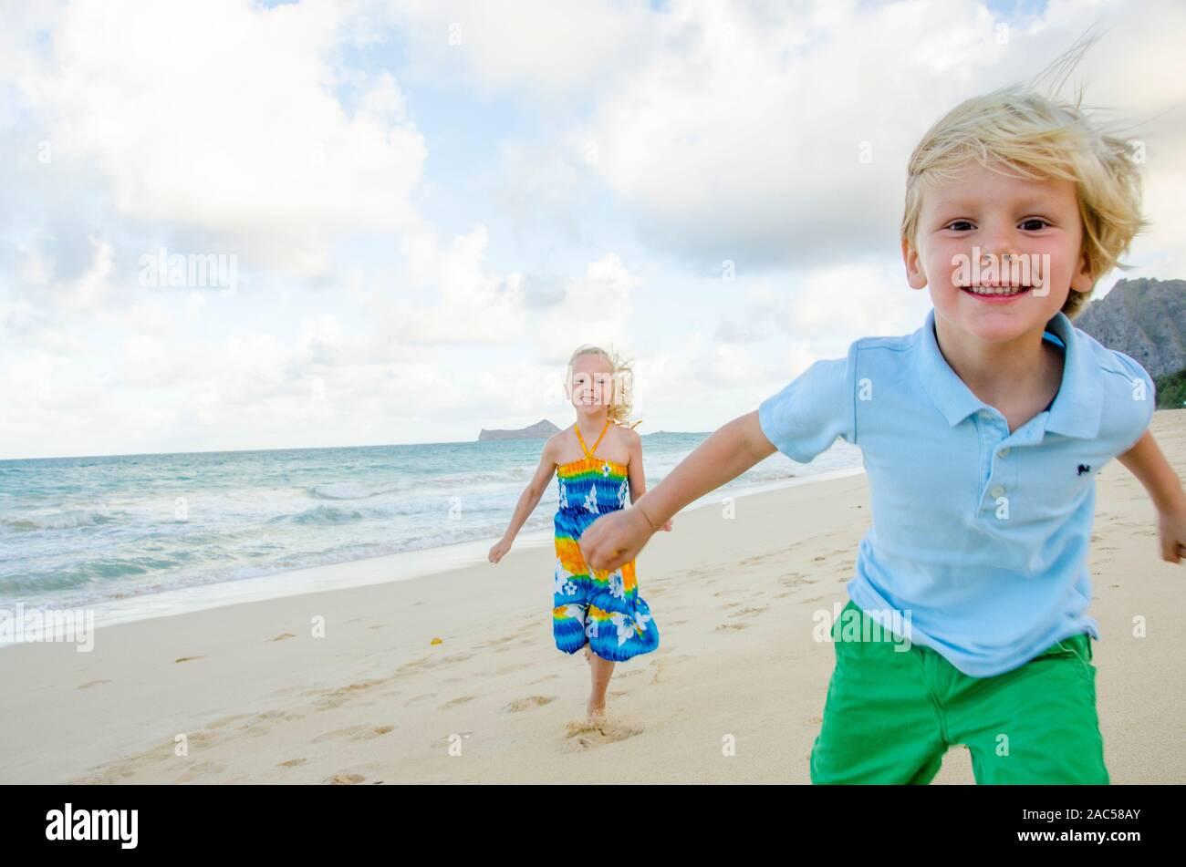 Dos niños jugando en la playa Waimanalo, O'ahu. Foto de stock