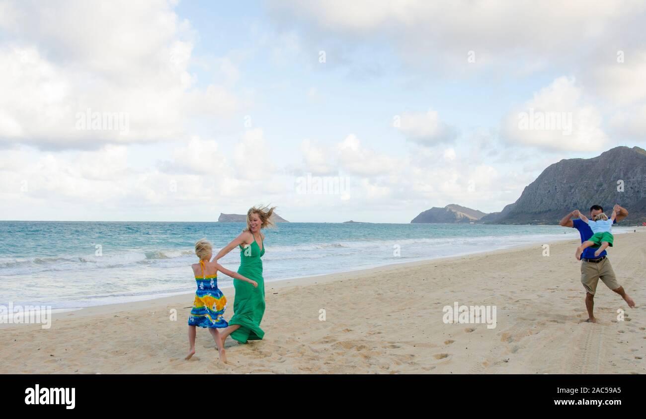 Una familia de cuatro personas jugando en Waimanalo Beach, O'ahu. Foto de stock