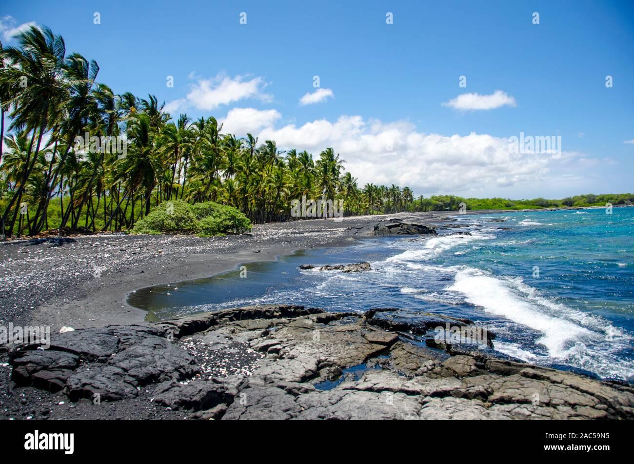 Mirando hacia el sur a lo largo de la mayoría de la playa de arena negra de Keawaiki Bay, al norte de kona, Hawai'i, una isla de 1859 erupción del volcán Mauna Loa fluyó en esta área, w Foto de stock
