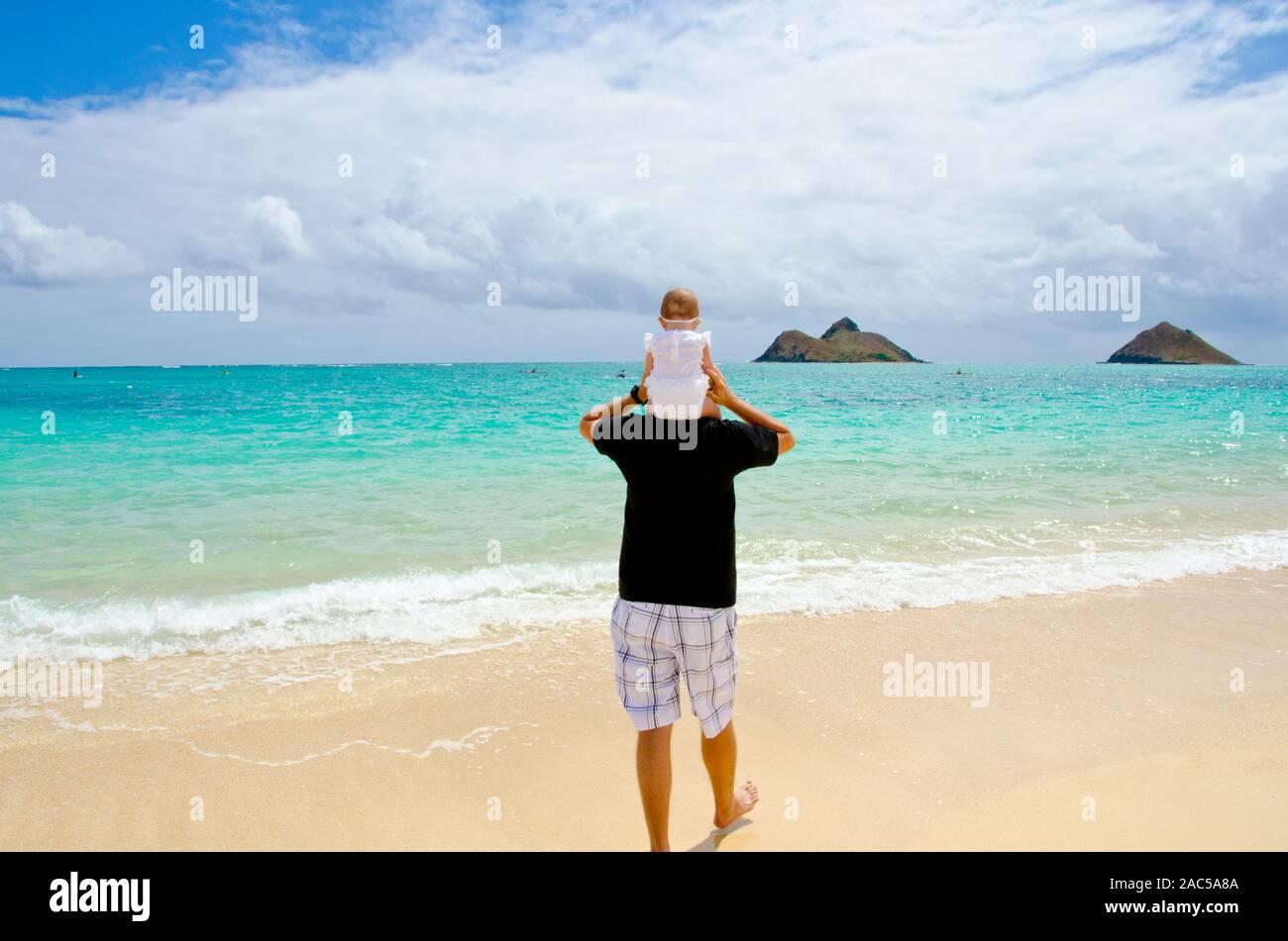 Papá Jason con el bebé Emma sobre sus hombros en Lanikai beach, Kailua, Oahu Foto de stock