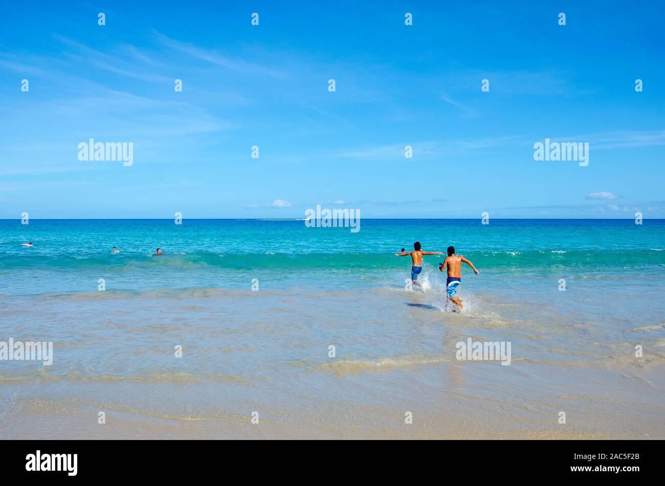Dos muchachos adolescentes corriendo hacia el océano en Hapuna Beach, a lo largo de la costa Kohala de la Isla Grande. Esta playa de arena blanca ha sido calificado como uno de los mejores bea Foto de stock