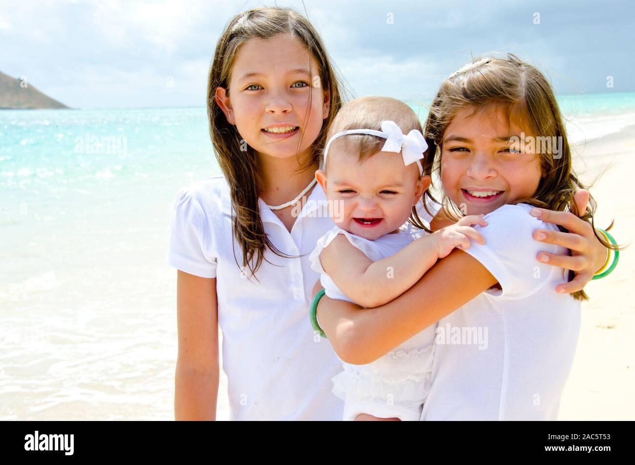 Hermanas Leilani y ke'alohi cuidando de su bebé en la playa hermana Emma Foto de stock