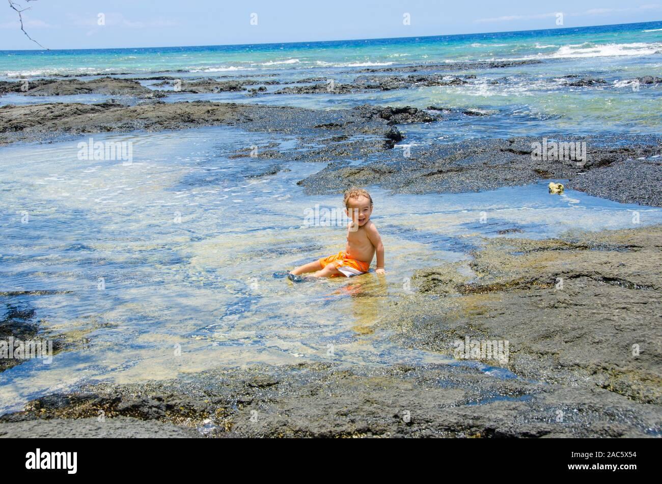 Un joven chico local se ríe como él se sienta en una piscina de marea en una playa en Puako, South Kohala, Hawai'i Isla. Foto de stock