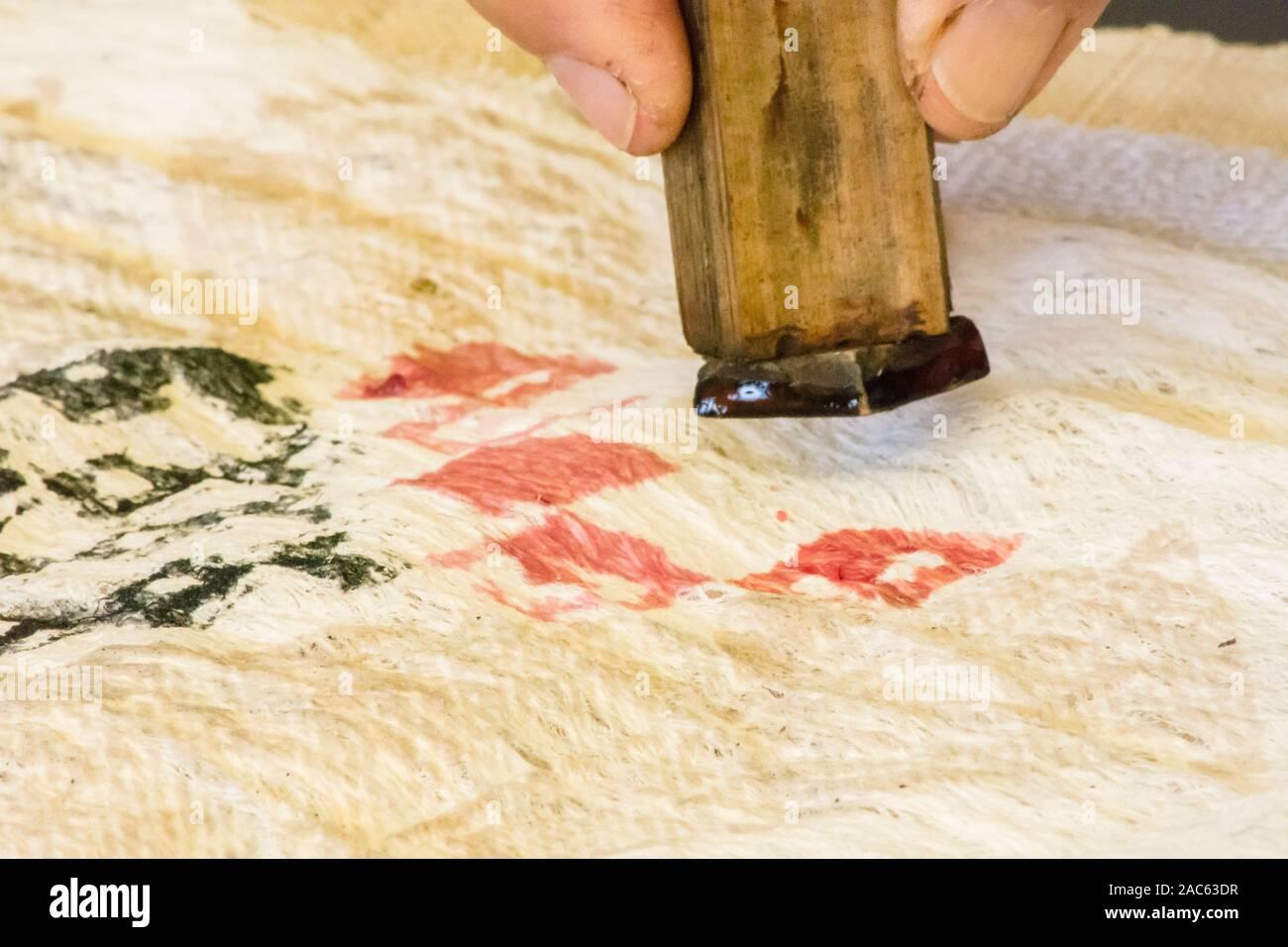 Kapa haciendo en la Isla Grande: Una kapa maker imprime diseños en kapa con un sello de madera impregnadas de tintes de plantas nativas. Foto de stock