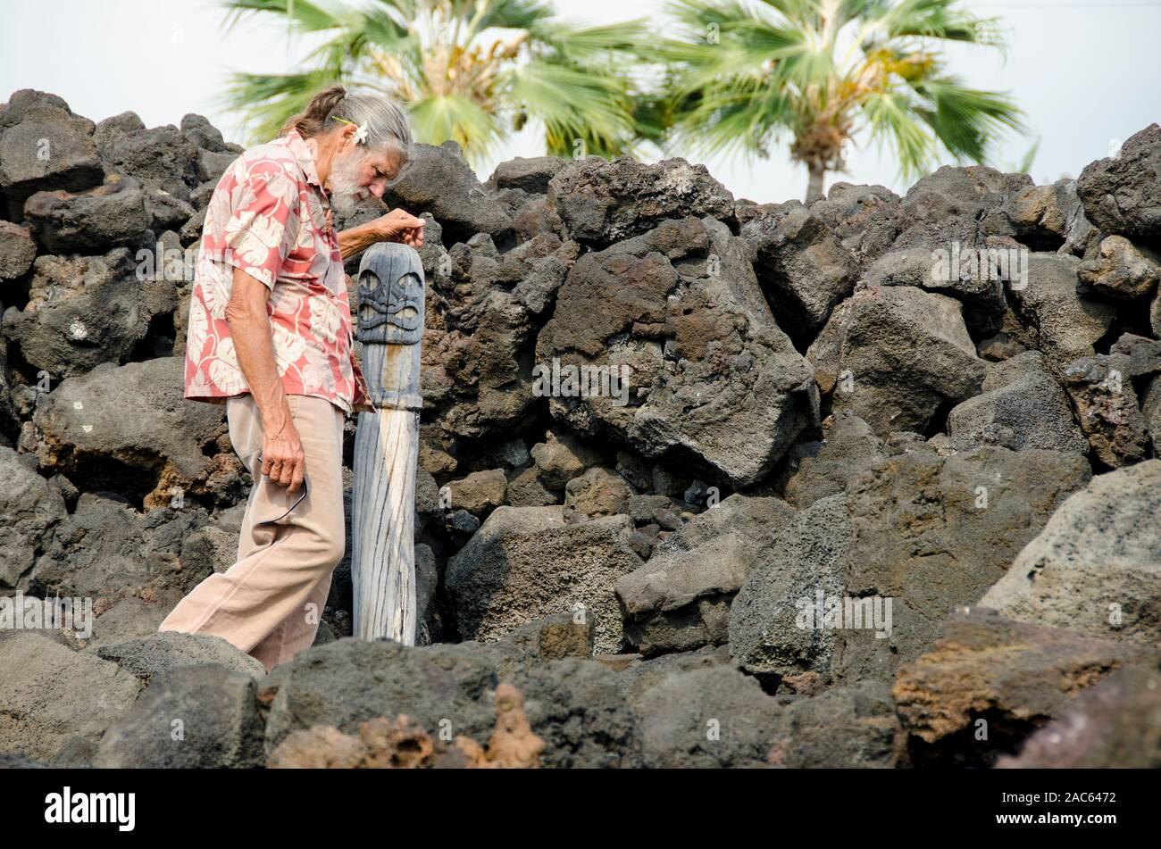 Artista Geno Bergmann cerca de una estatua tallada en madera que él creó hace muchos años para Kealakowa'un Heiau en Kailua-Kona, Isla Grande. Foto de stock